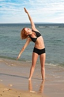 Beautiful red woman doing yoga exercises at the beach