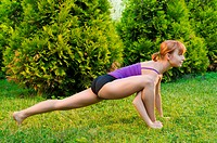 Beautiful young woman doing yoga exercises outdoors