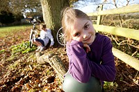 Girl sitting on log in meadow