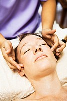 Woman having scalp massage in spa