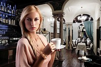 sensual blond girl with hair style drinking a cup of tea in elegant pink dress over dark fashion background