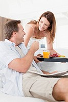 Woman bringing husband breakfast tray