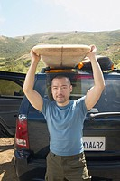 Man lifting surfboard from car rack