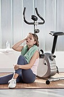 Woman wiping sweat by exercise machine