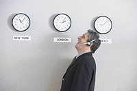 Businessman laughing in front of world time zone clocks