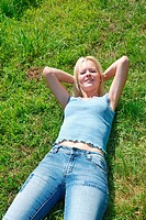 A beautiful young woman asleep in a grassy field
