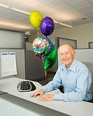 Senior businessman smiling in a cubicle with a bunch of retirement balloons