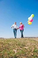 Middle-aged couple laughing as they walk across a meadow with colourful balloons in their hands