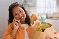 Young woman talking on her cell phone while holding a bag of groceries