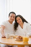Hispanic couple smiling at the breakfast table