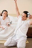 Hispanic couple playing video games in the bedroom
