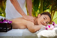 Young beautiful asian woman gets massage and beauty treatment in luxury resort. Side view