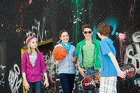 Teenagers standing in front of a wall with graffiti