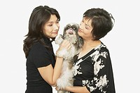 Studio shot of Asian mother and adult daughter with Shih_Tzu