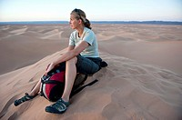 Young woman resting in the sand dunes of the Erg Chigaga Desert, Sahara, Morocco