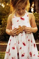 Girl holding gingerbread man outdoors