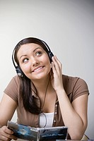 Teenaged Hispanic girl listening to music on headphones