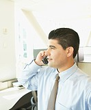 Hispanic businessman using telephone