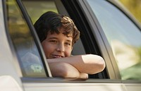 Boy smiling and leaning out of car window