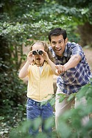 Hispanic father and daughter looking through binoculars