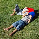Two boys laying on grass with buckets on heads