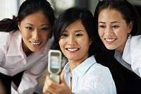 Asian businesswomen taking own photograph with cell phone