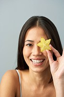 Asian woman holding star fruit over eye