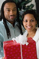 African couple holding gift in front of Christmas tree