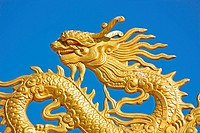 a gold dragon with a blue sky at a Buddhist temple
