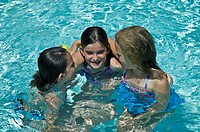 Three young girls talking and laughing together in a pool.