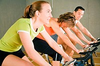 Three people spinning on stationary bicycles in the gym exercising for more fitness