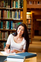 Portrait of a smiling student writing a paper in the library