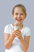 seven year old girl who is eating a chocolate ice cream