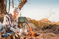Young hiking woman with backpack cook on campfire in countryside
