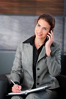 Young attractive personal assistant setting appointment on phone, smiling.