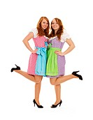 two bavarian dressed girls lifting their feet on white background