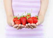 Girl hold fresh strawberries. Shallow DOF, focus on strawberries.