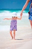 Adorable little girl walking in shallow water at Caribbean beach