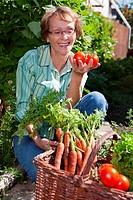 Senior woman in garden picking fresh produce