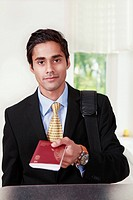 Young male traveler in business suit showing passport at a counter