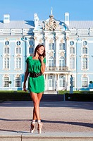 Beautiful ballerina is dancing outside with palace background