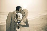 photograph of a bride and groom on the beach at sunset