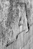 The letter A recessed into an old weathered concrete wall as a black and white imagez