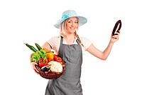 Full length portrait of a smiling female farmer holding various vegetables isolated on white background