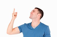 Smiling man pointing at something against a white background