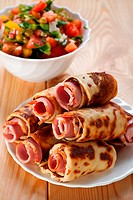 on wooden background, meat rolls bacon, ham, ham in the omelet, vegetable salad cucumbers, tomatoes, parsley