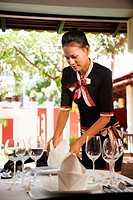 Attractive young woman working as waitress in exclusive restaurant, setting up a table. Waist up, side view