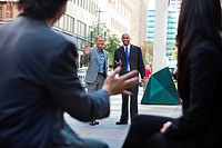 Business people waving and greeting friends on street