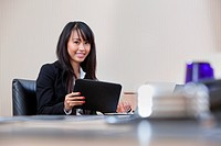 Portrait of smiling businesswoman working on digital tablet