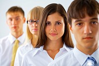 Portrait of young business woman with her colleagues standing in a row